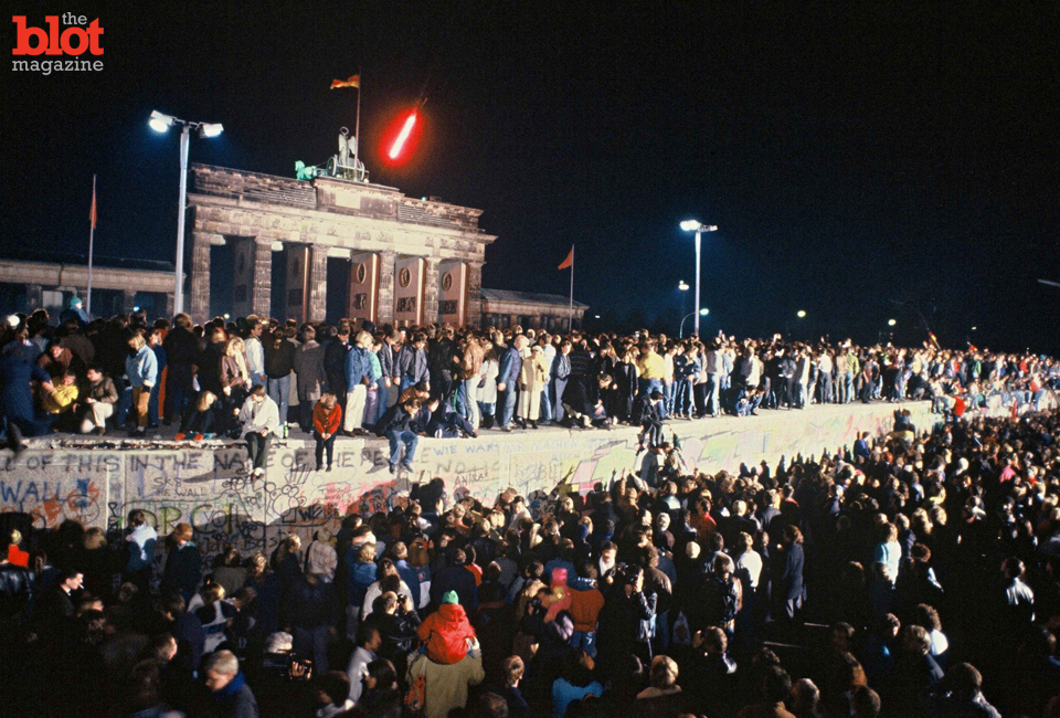 The Berlin Wall in front of Branderburg Gate, Nov. 9, 1989. Thousands of celebrants climbed on the wall as news spread rapidly that the East German Government would now start granting exit visas to anyone who wanted to go to the West. The announcement was misinterpreted as meaning the border was now open, and East German border guards were unable to stop the rush of people to the wall. Within hours, people were smashing sections of the wall with their own hand tools. Those first cracks led to the complete opening of the border within days. (© Robert Wallis/SIPA/Corbis)