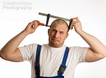 Construction worker holding bar clamp (c-clamp, screw clamp) over his head