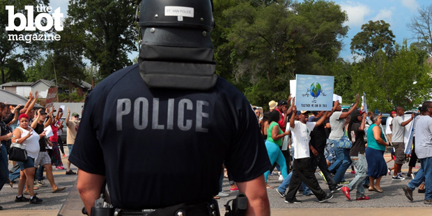 The DOJ criticized Ferguson police for racially profiling citizens for several years. It also released a 105-page report on the death of Michael Brown. In this photo from Aug. 11, a police officer in riot gear watches protesters march two days after Brown was shot by Officer Darren Wilson. (© Robert Cohen/ZUMA Press/Corbis photo)