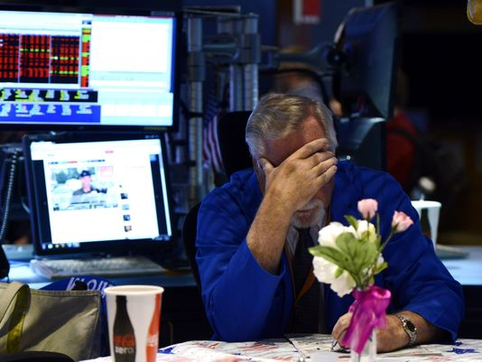 People are losing their minds over a tweet sent by an Anonymous-affiliated Twitter account predicting Wednesday's NYSE glitch that halted trading. Above, a trader sits at his desk during the three-plus hour halt. (USA Today photo)